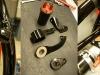 Czas na ogarnięcie licznych drobiazgów związanych z ramą. Trzeba dorobić nowe mocowanie górne silnika - bo nie było go w ogóle. Jak widać na foto uchwyt w ramie jest krzywo fabrycznie wspawany. Trzeba będzie ciąć, spawać i dopasowywać zarówno górny uchwyt jak i tzw. lizak amortyzatora skrętu. Na foto elementy po dopasowaniu, obróbce i lakierowaniu. Dorobiłem także nowe mocowanie cewki WN - stare było wykonane z grubej bednarki. Teraz wygląda to estetycznie.